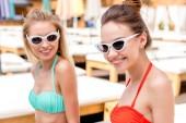 usměvavé mladé ženy v retro brýle při pohledu na fotoaparát v bazénu