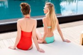 rear view of young women relaxing on sun lounger at poolside
