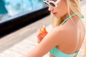 close-up shot of beautiful young woman applying sunscreen onto skin from spray bottle