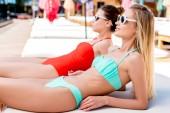 vonzó fiatal nők nyugágyon a medence mellett fekvő