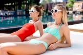 szép fiatal nők vintage napszemüveg nyugágyon a medence mellett fekvő