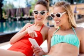 boldog, fiatal nők használ smartphone nyugágyon a medence mellett pihenve