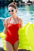 Fotografie usměvavá mladá žena v červené plavky s nafukovací matrace stojí u bazénu a ukazuje míru gesto