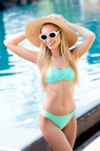 Szalma kalap vintage napszemüveg és a bikini, medence-vonzó fiatal nő