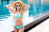Szalma kalap vintage napszemüveg és a bikini, medence-boldog fiatal nő