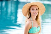 Fotografie attractive young woman in straw hat and bikini looking at camera at poolside