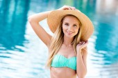 beautiful young woman in straw hat and bikini looking at camera at poolside