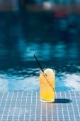 Nahaufnahme eines Glases köstlichen Orangencocktails am Pool