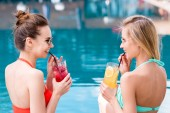 Fotografie beautiful young women drinking delicious fruit beverages at poolside and laughing