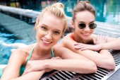 close-up portrait of happy young women relaxing in swimming pool and looking at camera