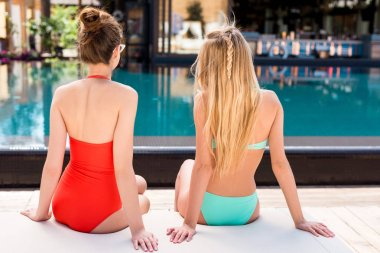 rear view of attractive young women relaxing on sun lounger at poolside