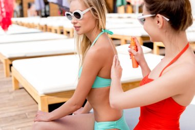 young woman applying sunscreen on shoulder of friend while they sitting on sun lounger