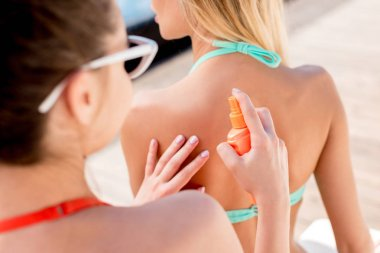 cropped shot of young woman applying sunscreen on shoulder of friend while they sitting on sun lounger