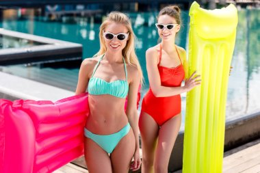 happy young women with inflatable mattresses standing at poolside