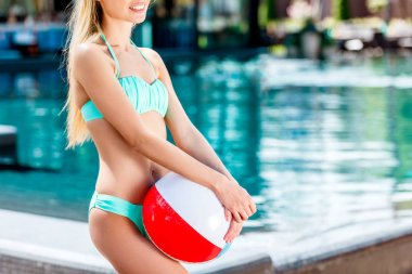 cropped shot of smiling young woman with beach ball at poolside