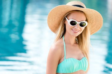 smiling young woman in straw hat with vintage sunglasses and bikini at poolside