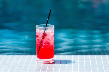 Close-up shot of glass of red berry cocktail on poolside stock vector