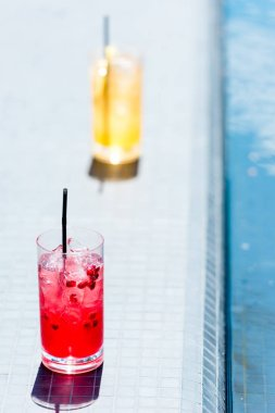 close-up shot of glasses of cocktails on poolside