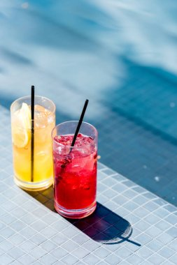 close-up shot of glasses of delicious fruit cocktails on poolside