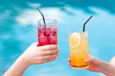 cropped shot of women clinking glasses of delicious cocktails in front of swimming pool