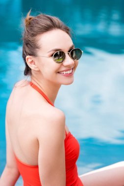 happy young woman in red swimsuit at poolside