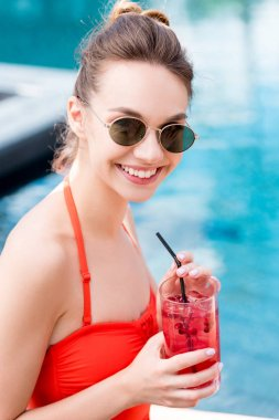 close-up portrait of happy young woman with berry cocktail at poolside