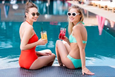 beautiful young women with delicious fruit beverages in glasses sitting at poolside and looking at camera