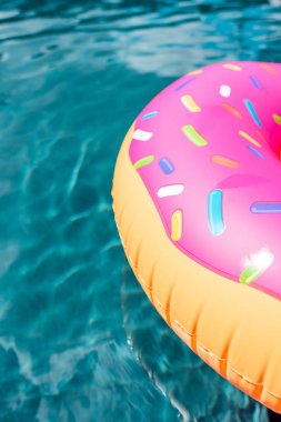 close-up shot of inflatable ring in shape of donut floating in swimming pool
