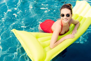 attractive young woman lying on inflatable mattress in swimming pool