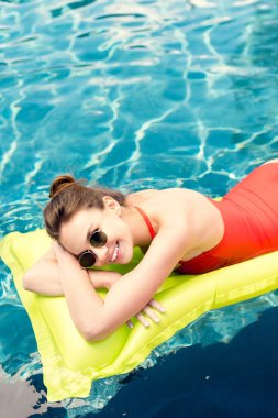 Happy young woman lying on inflatable mattress in swimming pool stock vector