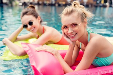 beautiful young women lying on inflatable mattresses in swimming pool and looking at camera
