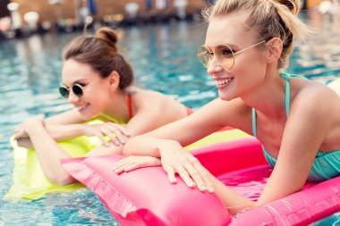 happy young women lying on inflatable mattresses in swimming pool