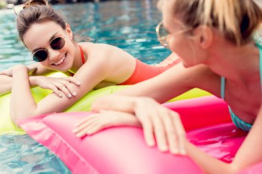 attractive young women lying on inflatable mattresses in swimming pool