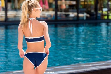 rear view of attractive young woman in stylish bikini at poolside