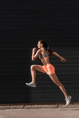 young athletic female runner training in sportswear