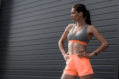young sporty girl posing in sportswear with fitness tracker