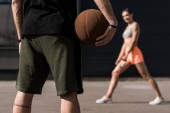 selective focus of sportsman with basketball ball and sportswoman stretching on background