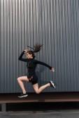 Fotografia giovane sportiva in Abbigliamento termico sportivo nero che salta in città