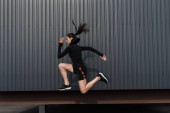 athletic woman in black thermal clothes jumping in city