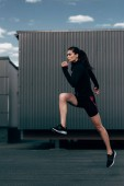 young sportswoman in black thermal clothes jumping in city