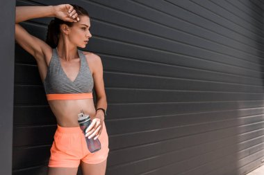 sportswoman with fitness tracker and bottle of water