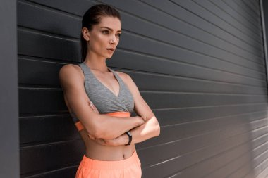 young confident sportswoman posing with crossed arms and fitness tracker