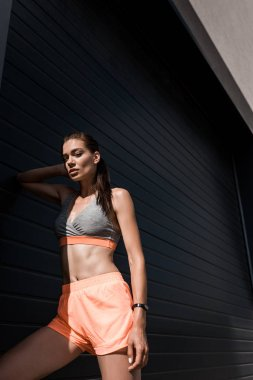 athletic woman posing in sportswear with fitness tracker
