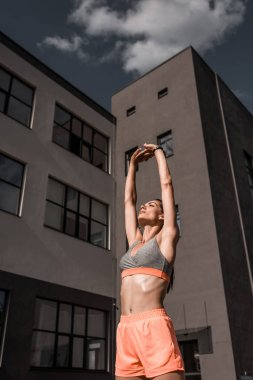 young sportswoman stretching arms in city