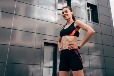 young smiling sportswoman with fitness tracker
