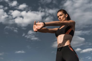 attractive sportswoman stretching hands against blue cloudy sky
