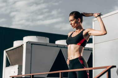 young sportswoman with ponytail in sportswear on roof