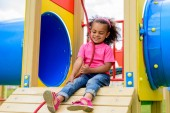 happy curly african american little child having fun at playground