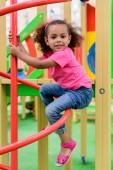 s úsměvem kudrnaté africké americké malé dítě baví u hřiště
