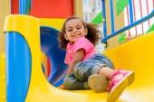 glücklich afroamerikanische Geißlein abrutschen vom Hügel am Spielplatz